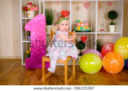 Cute funny little child in first birthday with colored balloons in the bright room - stock photo