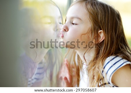 Cute funny little girl kissing her reflection on a window glass - stock photo