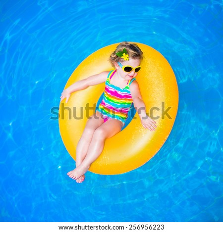 Cute funny little toddler girl in a colorful swimming suit and sun glasses relaxing on an inflatable toy ring floating in a pool having fun during summer vacation in a tropical resort  - stock photo