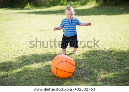 Cute funny smiling baby playing with a ball in a sunny summer garden - stock photo