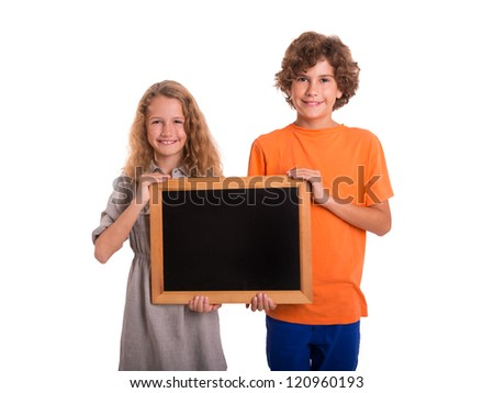 Cute girl and boy hold a small blackboard and are smiling into the camera - stock photo