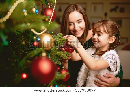 Cute girl and her mother decorating firtree on Christmas eve - stock photo