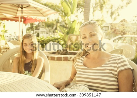 Cute girl and her mother eating at an outdoor cafe - stock photo