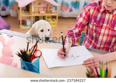 Cute girl and puppy drawing together at kids room - stock photo