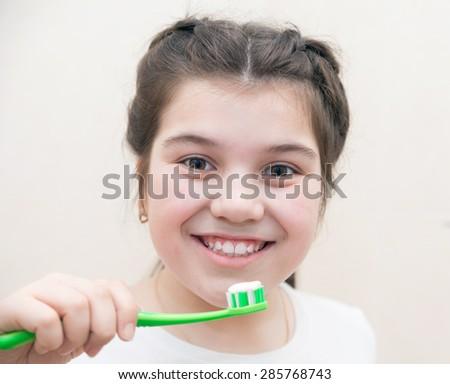 cute girl brushing her teeth in   bathroom.  - stock photo