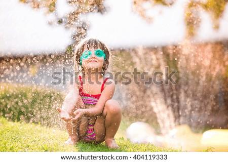 Cute girl crouching under the water splashing from sprinkler - stock photo