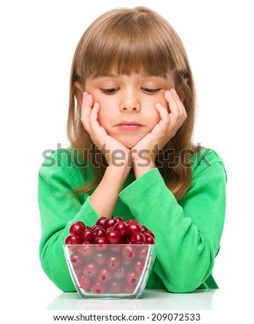 Cute girl doesn't want to eat cherries, isolated over white - stock photo