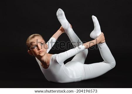 cute girl doing fitness exercises over black background - stock photo