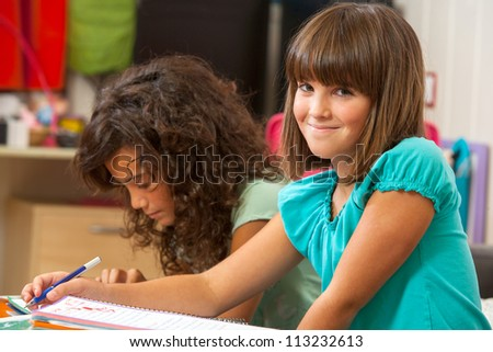 Cute girl doing homework with friend at home. - stock photo