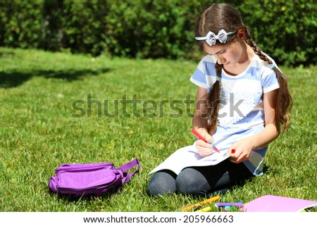 Cute girl drawing in park - stock photo