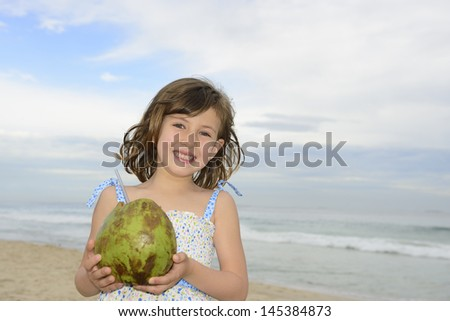 cute girl drinking coconut water on beach - stock photo