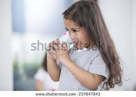 Cute girl drinking glass of water at home - stock photo