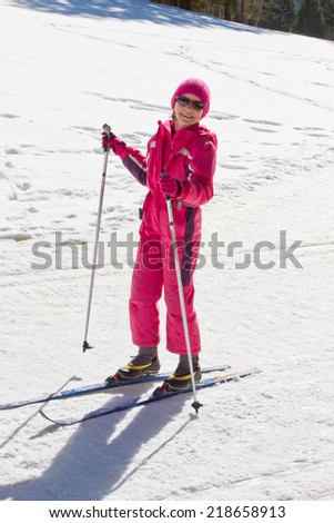 Cute girl enjoying cross country skiing on a sunny day - stock photo