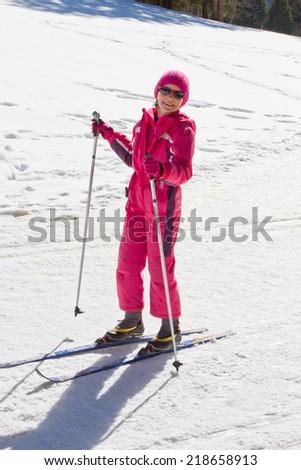 Cute girl enjoying cross country skiing on a sunny day - stock photo