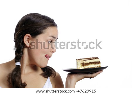 Cute girl eyes a piece of cake - stock photo