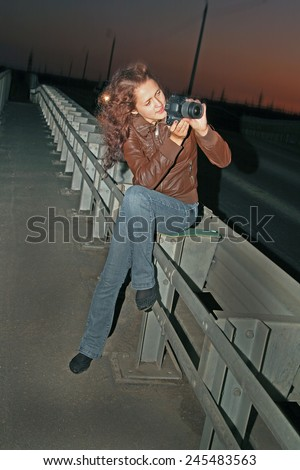 Cute girl full length tourist sit on metal car bridge  taking photos with black modern photo camera Woman wear casual dress blue sexy jeans on slim long legs and brown leather jacket Night image - stock photo