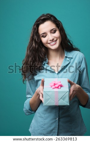 Cute girl giving a beautiful gift box with pink ribbon - stock photo