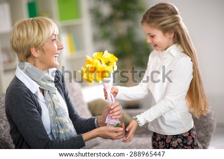 Cute girl giving a bunch of flowers to her grandmother - stock photo