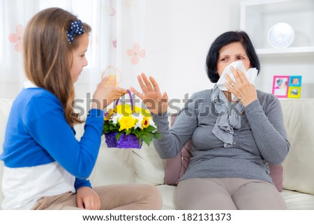 Cute girl giving a bunch of flowers to her grandmother. Grandmother has an allergy to flowers. - stock photo