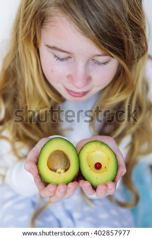 Cute girl hold avocado in her hands - stock photo