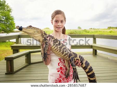 Cute girl holding a crocodile near florida everglades - stock photo