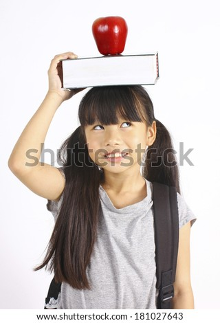 Cute girl holding book and apple on the head  - stock photo