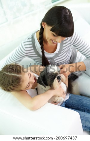Cute girl holding pet and looking at it with her mother near by - stock photo
