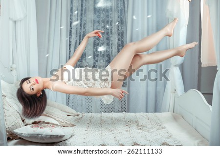 Cute girl hovers over the bed in the air without touching the bed. - stock photo