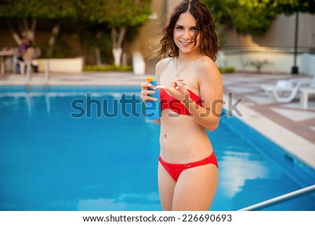 Cute girl in a bikini about to put some suntan on her face before going into the pool - stock photo