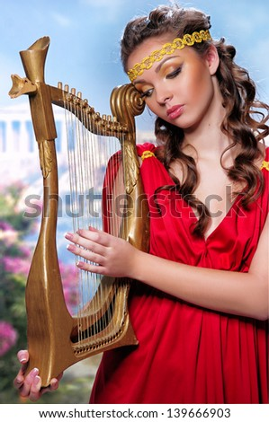 cute girl in a red tunic with a harp on a background of Greece - stock photo