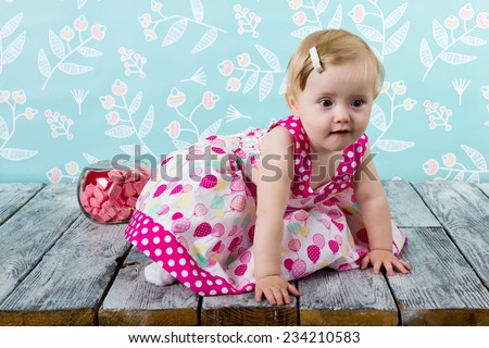 Cute girl in dress sitting on the floor among the flowers and interior items - stock photo
