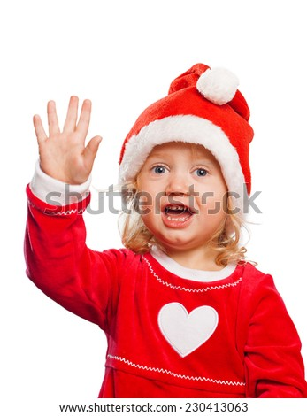 cute girl in Santas clothing waving her hand isolated on white background - stock photo