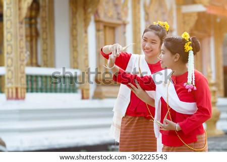 Cute girl in Thai tradition costume are studying Thai dance in temple. picture focus at a behind girl face and blur temple as background. - stock photo