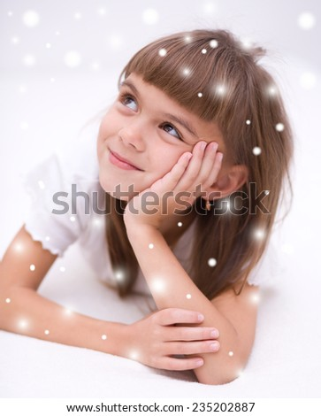 Cute girl is daydreaming lying on the floor, over snowy background - stock photo