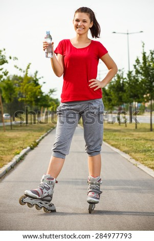 Cute girl is drinking water after roller skating.Refreshment after roller skating - stock photo