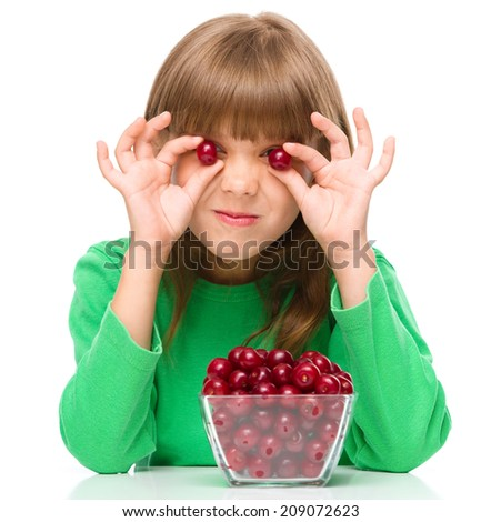 Cute girl is eating cherries and using them as an eyes, isolated over white - stock photo