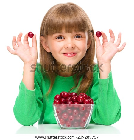 Cute girl is eating cherries, isolated over white - stock photo