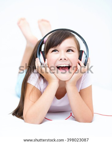 Cute girl is enjoying music using headphones and closed her eyes - stock photo