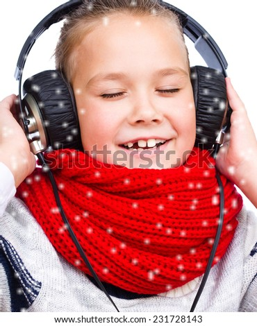 Cute girl is enjoying music using headphones, over snowy background - stock photo
