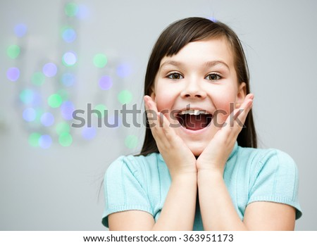 Cute girl is holding her face in astonishment - stock photo