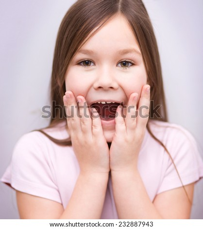 Cute girl is holding her face while listening to somebody - stock photo