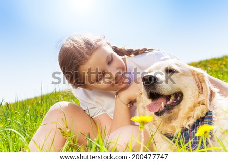 Cute girl looking close at dog and hugging it - stock photo