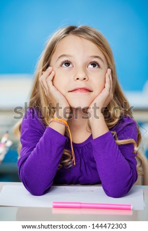 Cute girl looking up while sitting with head in hands in drawing class - stock photo