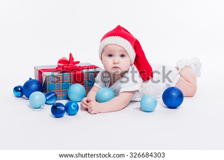 Cute girl lying on her stomach on a white background in a New Year's cap among Christmas balls, blue and red boxes with gifts, picture with depth of field - stock photo