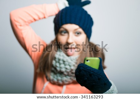 cute girl making a funny self photo dressed in winter clothes. hipster, on a gray background - stock photo