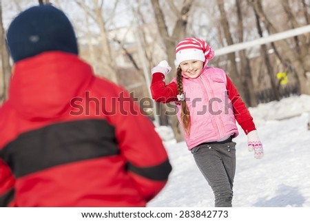 Cute girl of school age having fun in winter park - stock photo