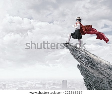 Cute girl of school age in superhero costume - stock photo