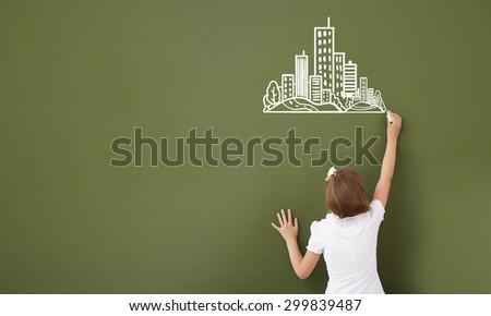 Cute girl of school age writing with chalk on blackboard - stock photo