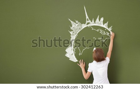 Cute girl of school age writing with chalk on blackboard - stock photo