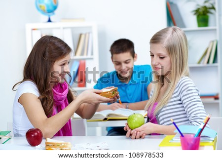 Cute girl offering her friend a sandwich during break in college - stock photo